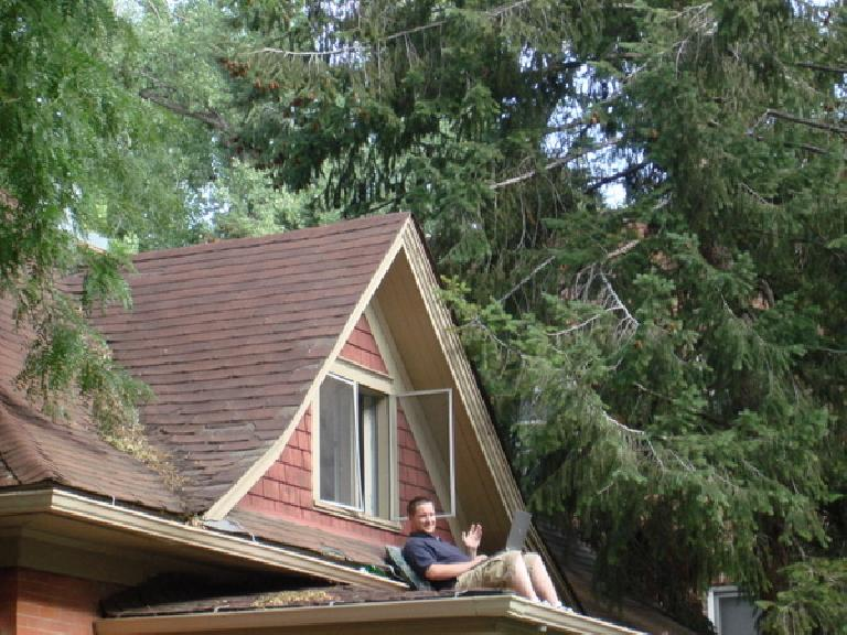 A guy with a laptop on the roof of his house waves. Photo: Ann Podbielski.