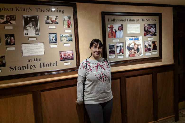 Vicky in front of photos of Hollywood movies filmed at the Stanley Hotel.