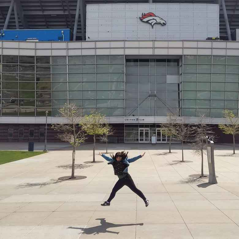 Vicky jumping in front of Mile High Stadium, where the Denver Broncos play their home games.