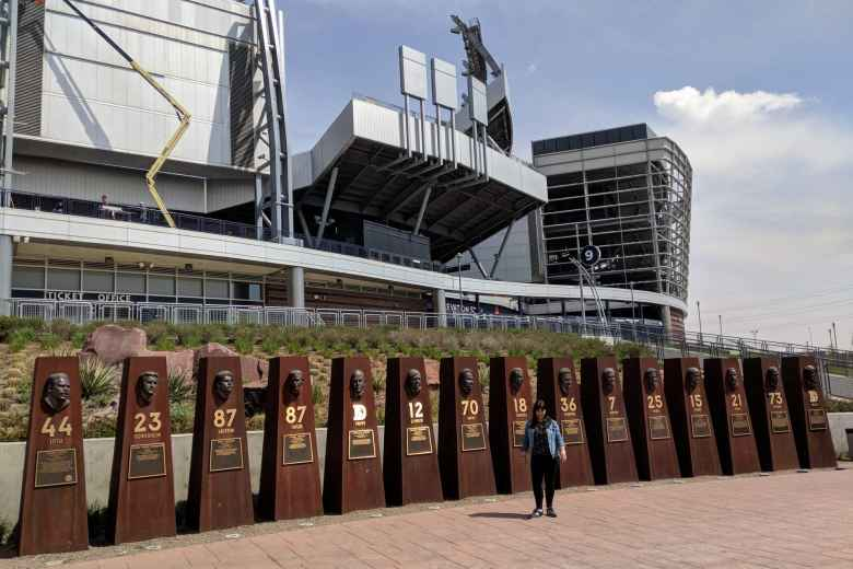 Vicky by large outdoor plaques for Denver Broncos players in the Hall of Fame.