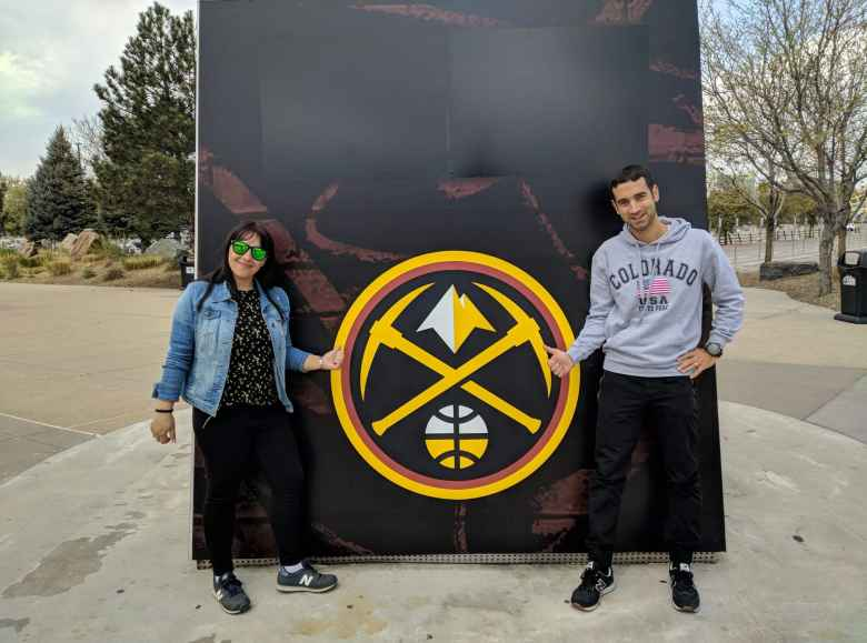 Vicky and Antxon in front of the Denver Nuggets new logo at the Pepsi Center.