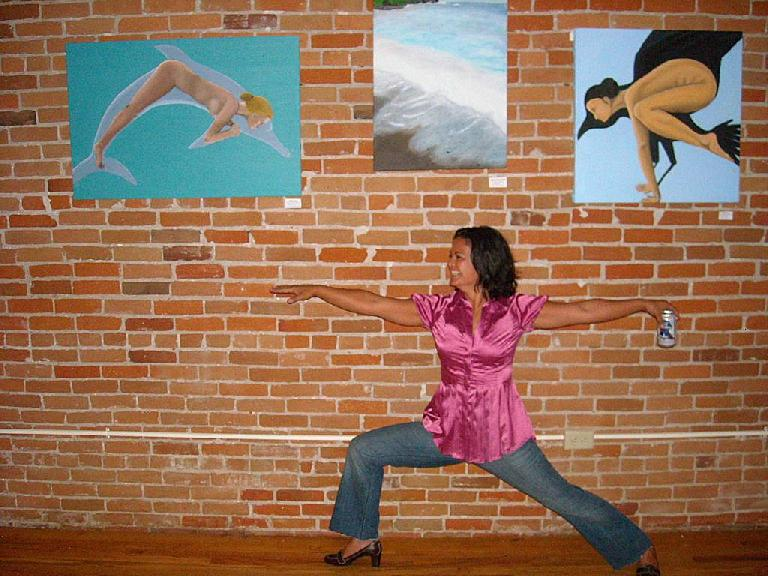 Sammie doing a yoga pose underneath her art work at Old Town Yoga.