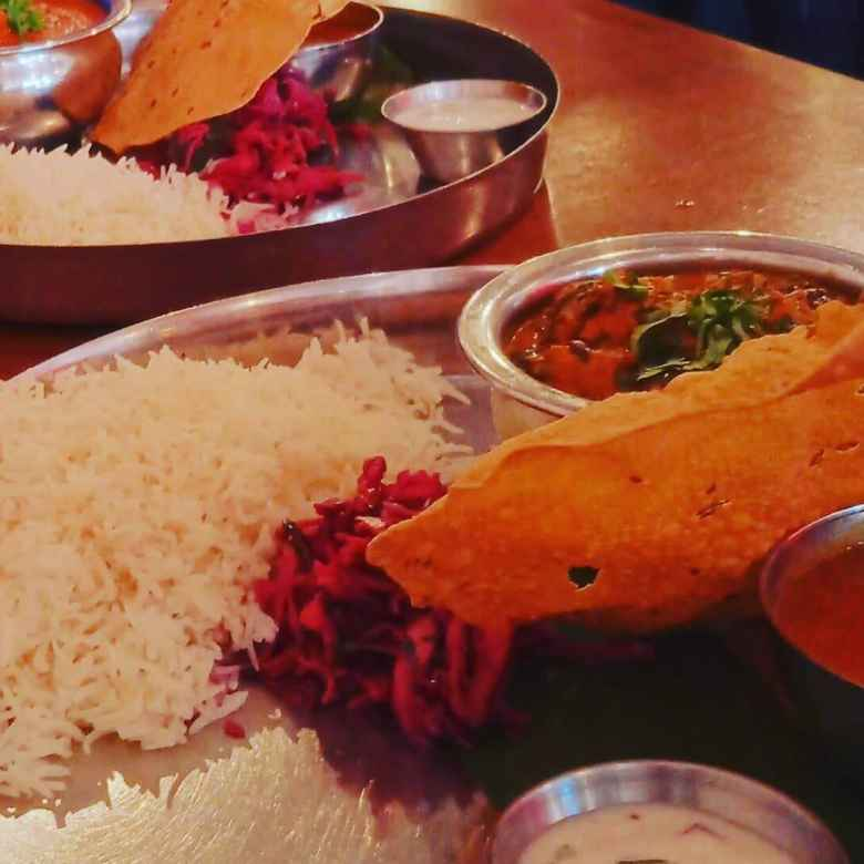 Saag Paneer and Chicken Thali with rice, slaw, and papadams at Chai Pani in Asheville.