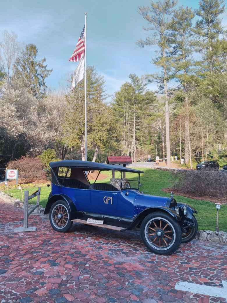 A blue antique car and a U.S. flagpole in front of the Grove Park Inn in Asheville, North Carolina.
