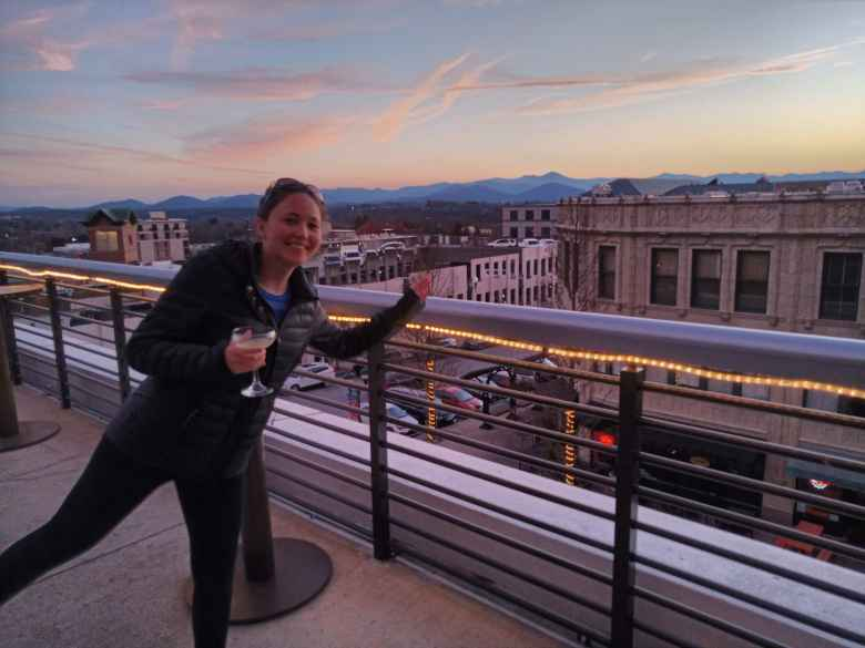 Maureen on the rooftop patio of Hemingway's Cuba in Asheville, with a nice sunset behind.