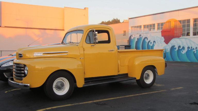 vintage yellow Ford pickup truck, blue wave mural, Astoria, Oregon