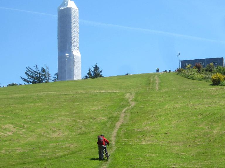 A cyclist walking up a hill to the Astoria Column.