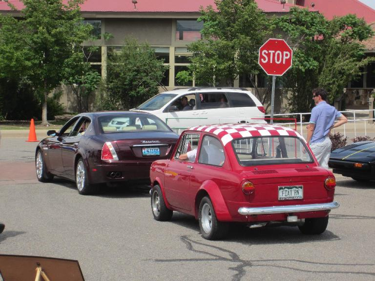 A 1960s Fiat following a Maserati Quattroporte.