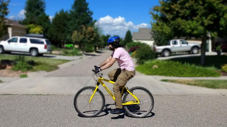 Azad riding a yellow 1996 Cannondale F700 hardtail mountain bike.