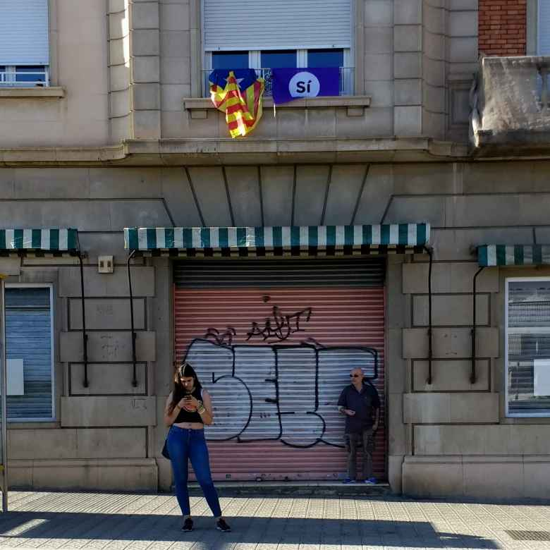 """A woman looking at her smartphone underneat the Catalunya flag and """"Sí"""" banner (for the upcoming referendum for independence) in Barcelona, Spain."""