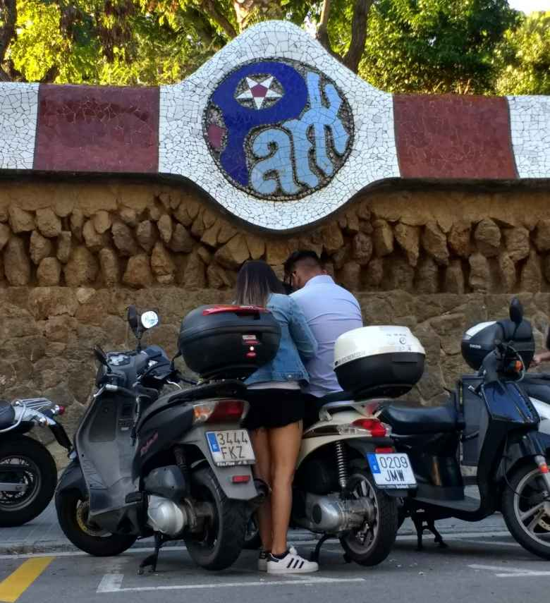 A woman with a man on a motorbike underneat the Park Güell sign.