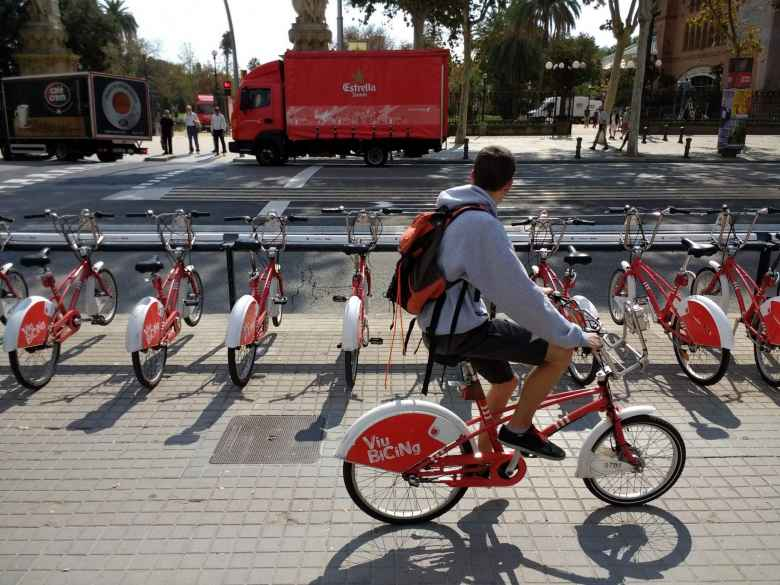 A commuter biking past the row of red and white Bicing city share bicycles.