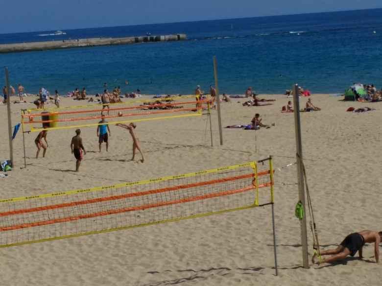 Folks playing beach volleyball, and a man doing pushups, at la Platja de la Nova Icària in Barceloneta.