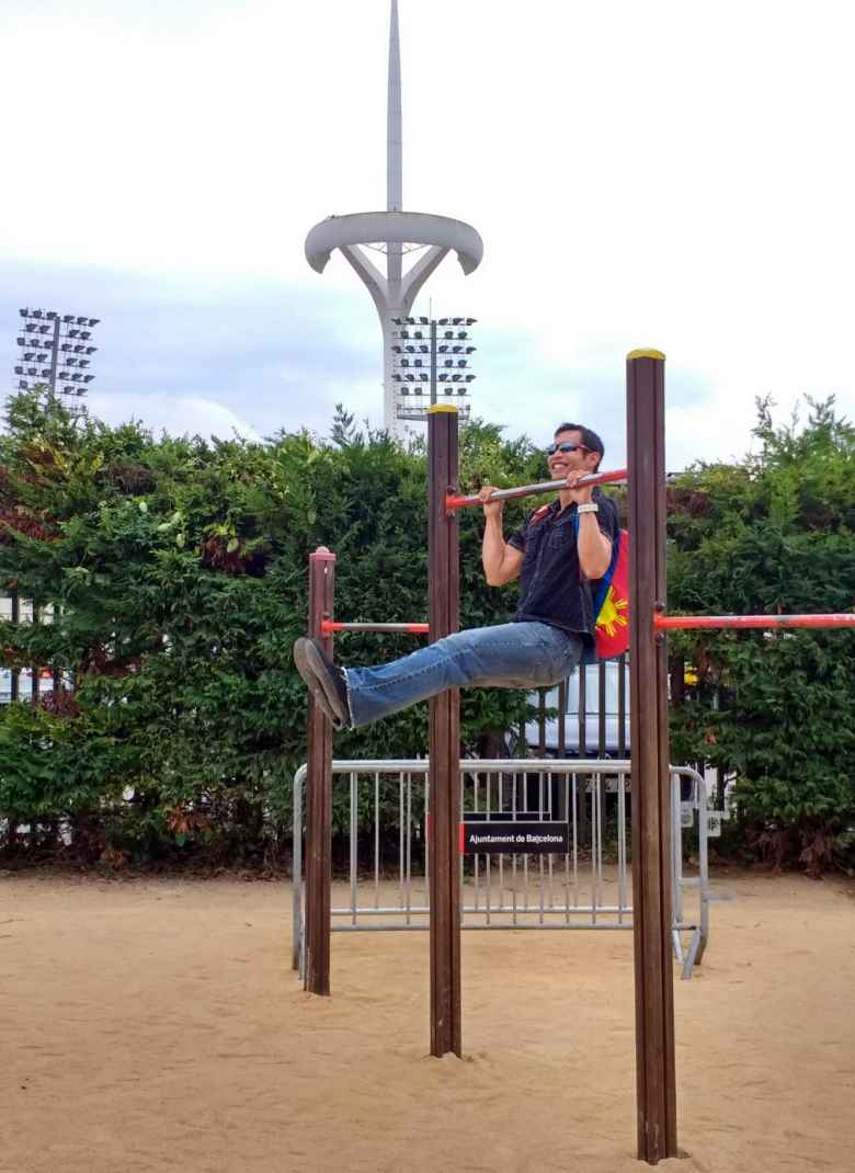 Felix Wong doing pull-ups wearing a backpack in front of the Olympic Stadium in Barcelona, Spain.