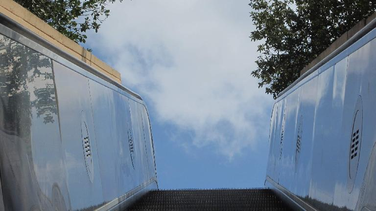 Clouds above the top of an escalator.