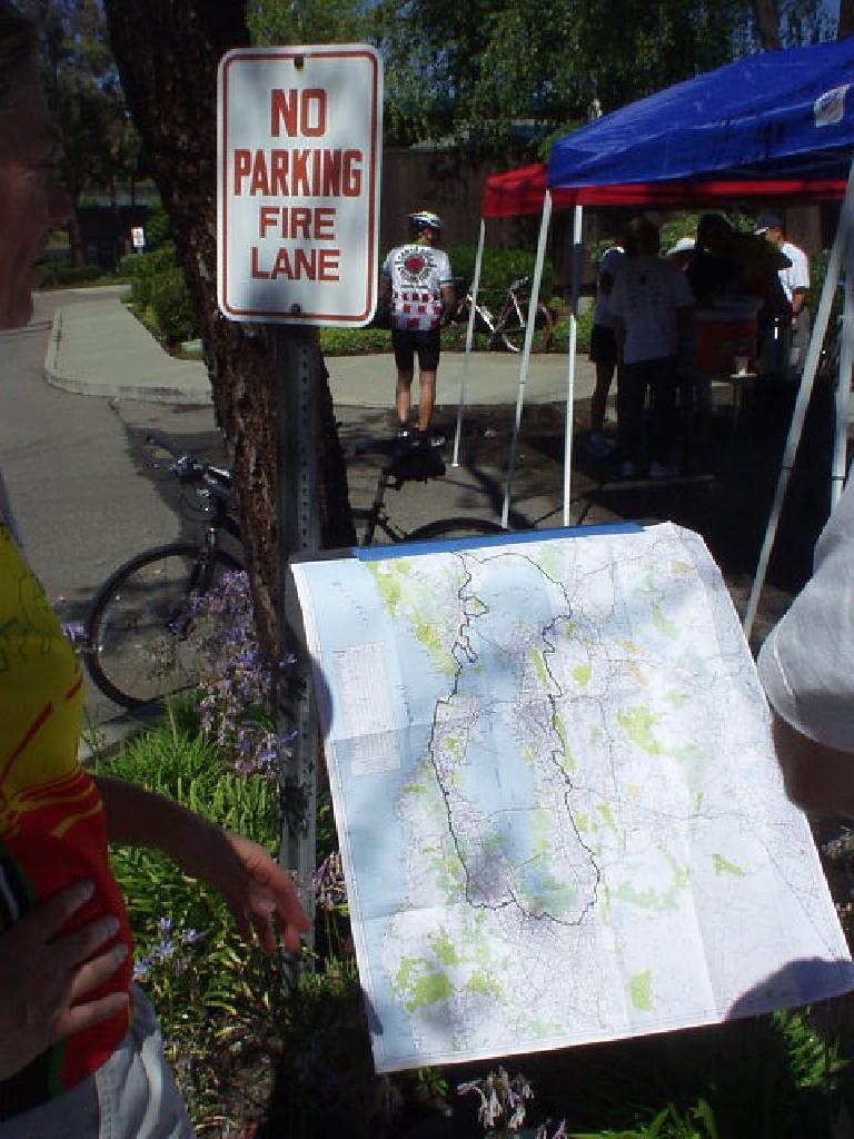 "[Mile 73, 10:41 a.m.] At Rest Stop #3, several cyclists inspect a map of the route we would follow today.  It does put the distance into perspective a bit, as in ""this is nuts!"""