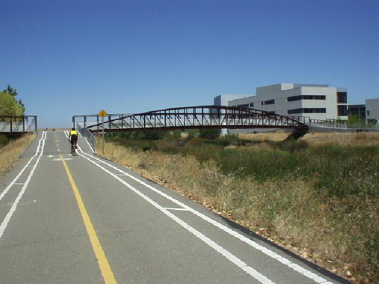 [Mile 99, 12:58pm] A cyclist approaches a bridge on a bike path in Milpitas.