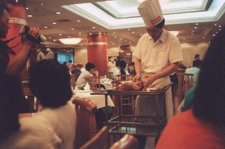 "A chef preparing Peking duck for dinner at ""Beijing's best Peking duck restaurant"" with our tour group's ""Captain Video"" filming at the left. (May 28, 2002)"