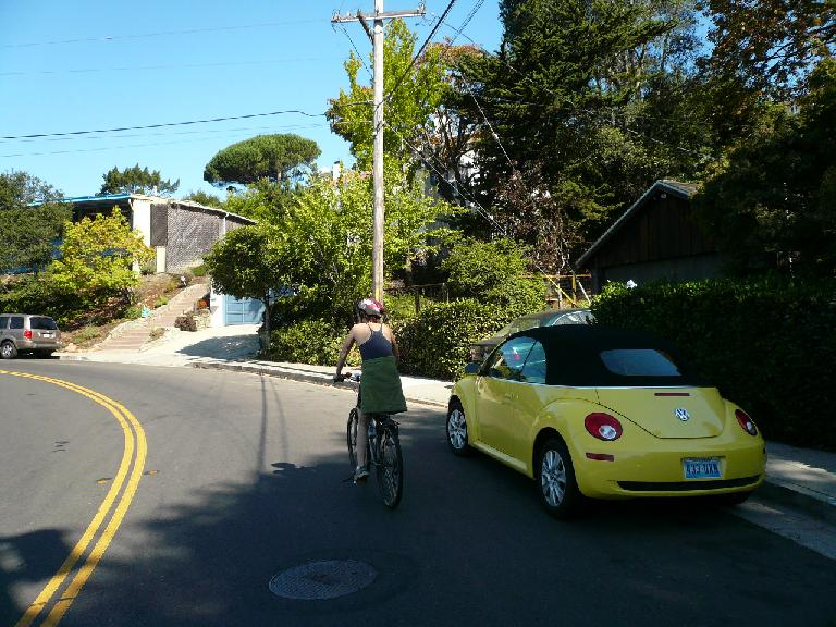 Sarah going up Spruce St., past a yellow Beetle.