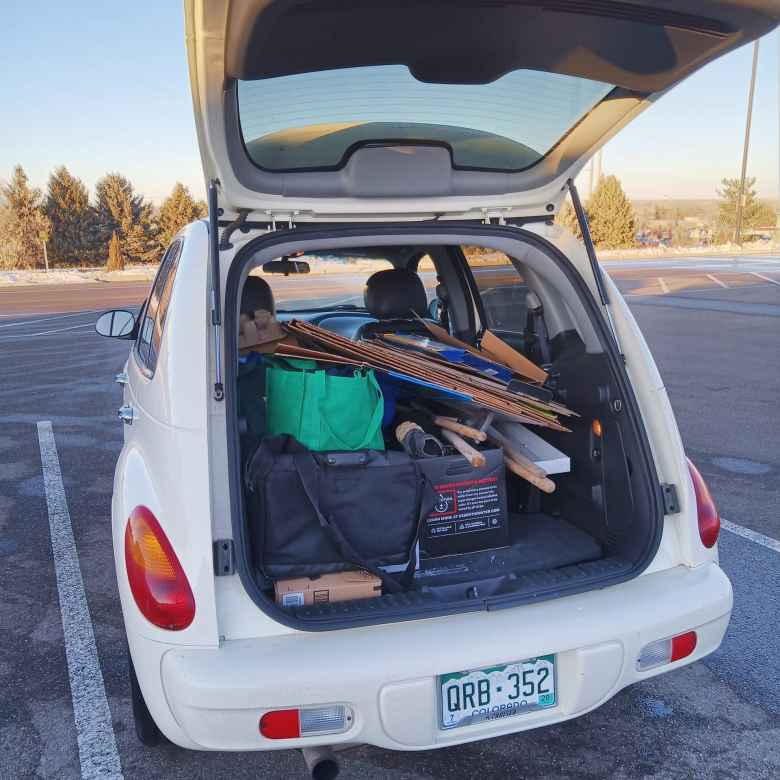 white 2005 Chrysler PT Cruiser, carboard boxes and cloth bags in cargo space, hatch open