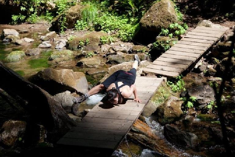 Alyssa doing a yoga pose on a bridge without falling into the river. Photo: Bryan O'Connor.