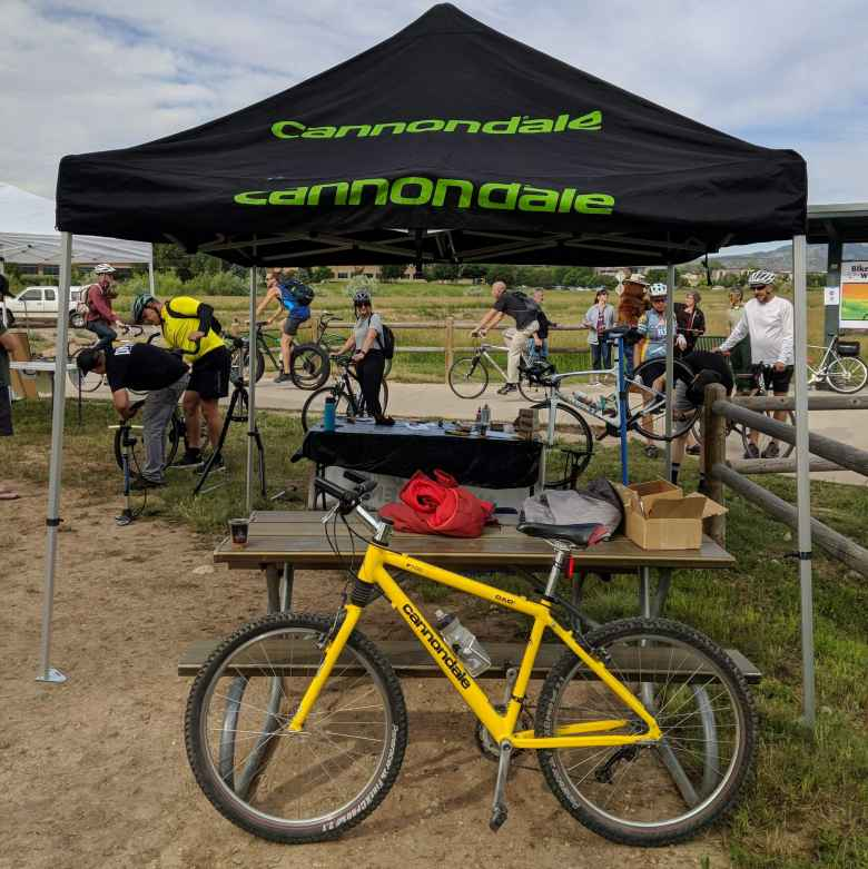 My yellow 1996 Cannondale F700 in front of a Cannondale tent.