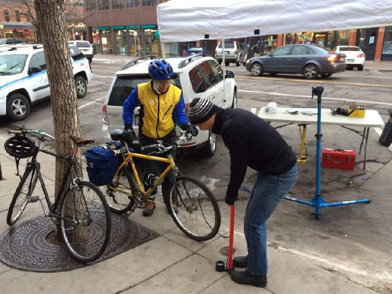 Felix Wong pumping up a commuter's front bicycle tire during Fort Collins Winter Bike to Work Day.