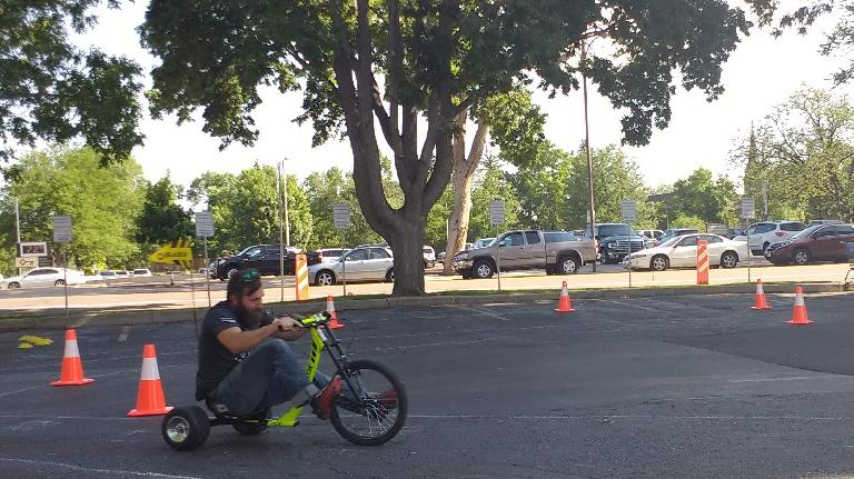 Riding a tricycle around a parking lot course at a Fort Collins Bike to Work Day station off Meldrum and Oak Street.
