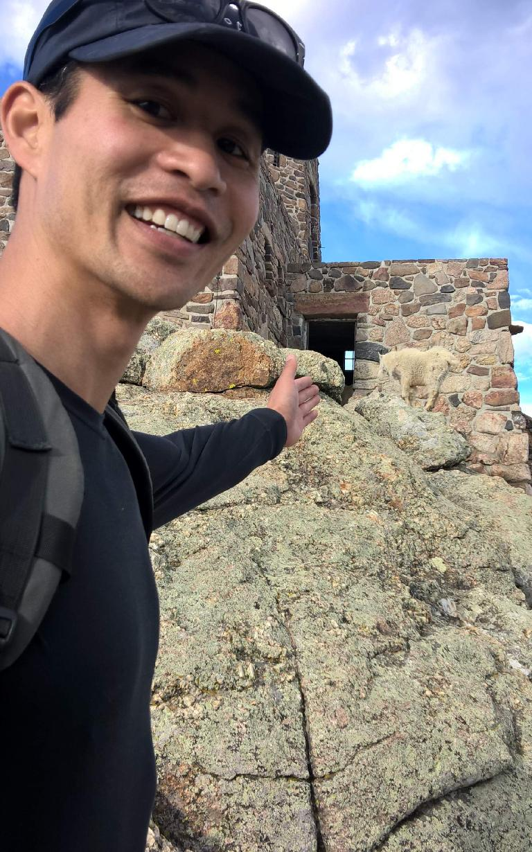 Felix Wong and a mountain goat at the stone lookout tower at the top of Harney Peak.