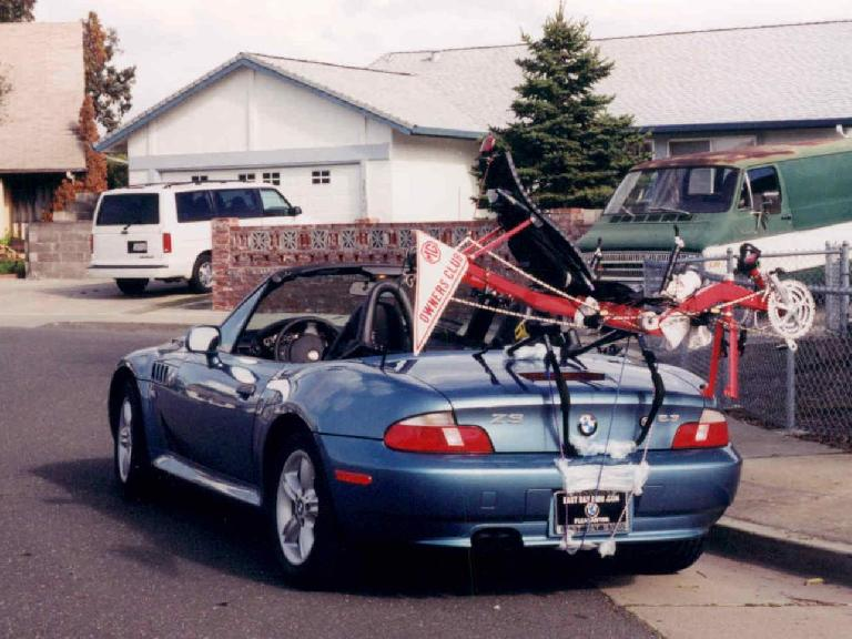 blue 2000 BMW Z3, top down, red Reynolds Wishbone recumbent frame on bike rack