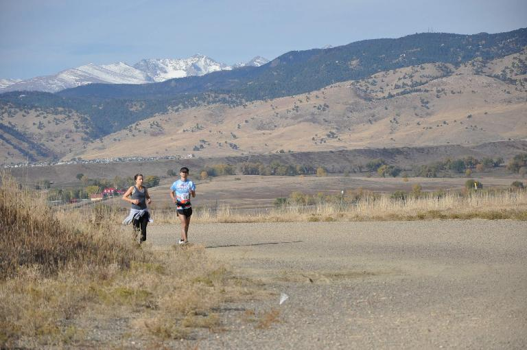 [Mile 95, 10:00a] Running with my sweetie with the Rocky Mountains peering over the Front Range behind. Photo: Eddie Metro.