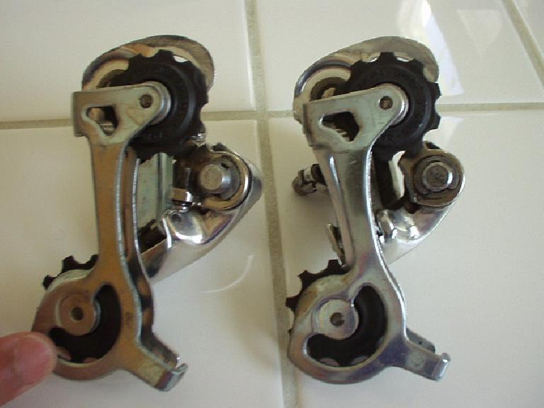 I was riding off-road (on my road bike, and a long piece of barbed wire got tangled in the rear wheel, seizing the wheel.  When the wheel seized, the tension tab on the rear derailleur (Campagnolo Veloce, above right) broke off. (On the left is an identical, unbroken derailleur for comparison.) (June 12, 2004)