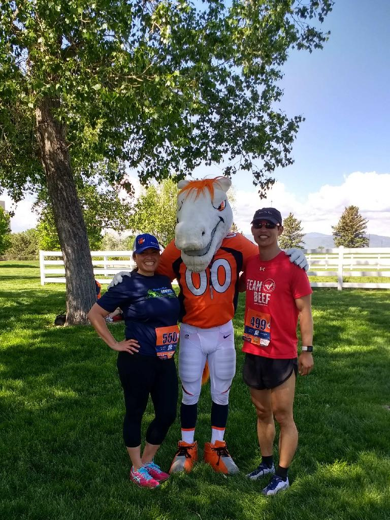 Raquel, Miles the Mascot, and Felix Wong after the 2017 Broncos 7k run in Fort Collins.