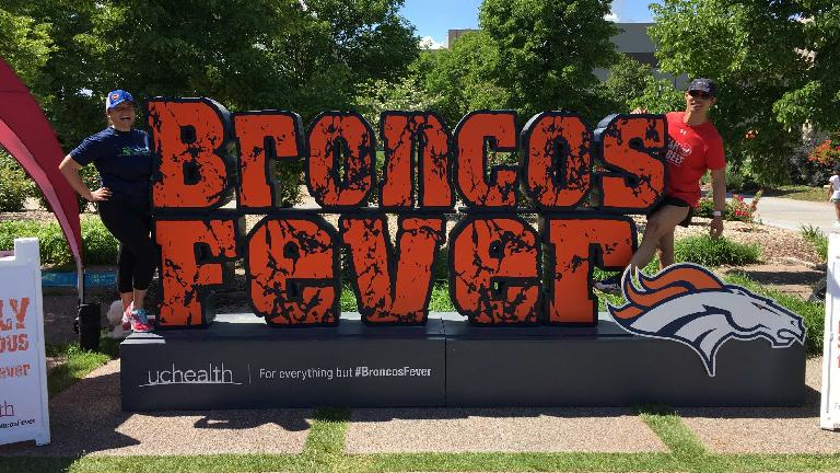 Raquel and Felix in front of a Broncos Fever sign at the 2017 Broncos 7k in Fort Collins.