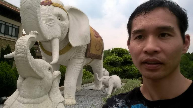 Felix Wong with elephant statues at the Buddha Memorial Center in Taiwan.