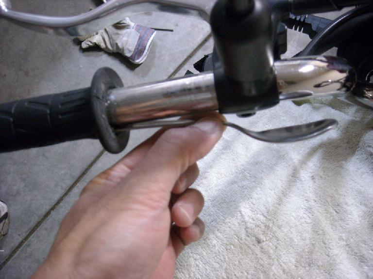 I used a spoon handle and then a flat screw driver to unstick the left grip from the handlebars.