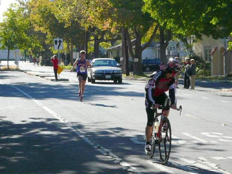 The first runner was so far ahead that he cruised into the finish behind this cyclist.