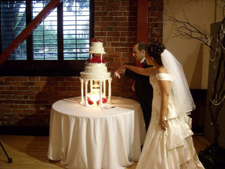 Trang and Naoum cut their wedding cake.