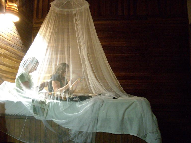 Tori and Raquel under mosquito netting back at the Kelly Creek Hotel in Cahuita.