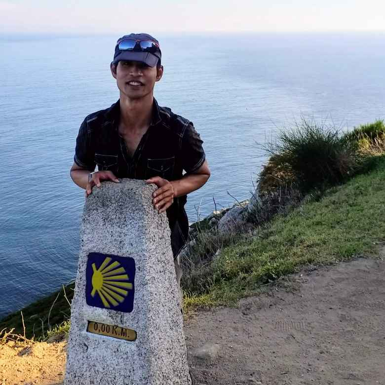 Felix Wong by the Kilometer 0.00 marker of the Camino de Santiago/Camiño de Fisterra. The walk across the entire country of Spain was complete!