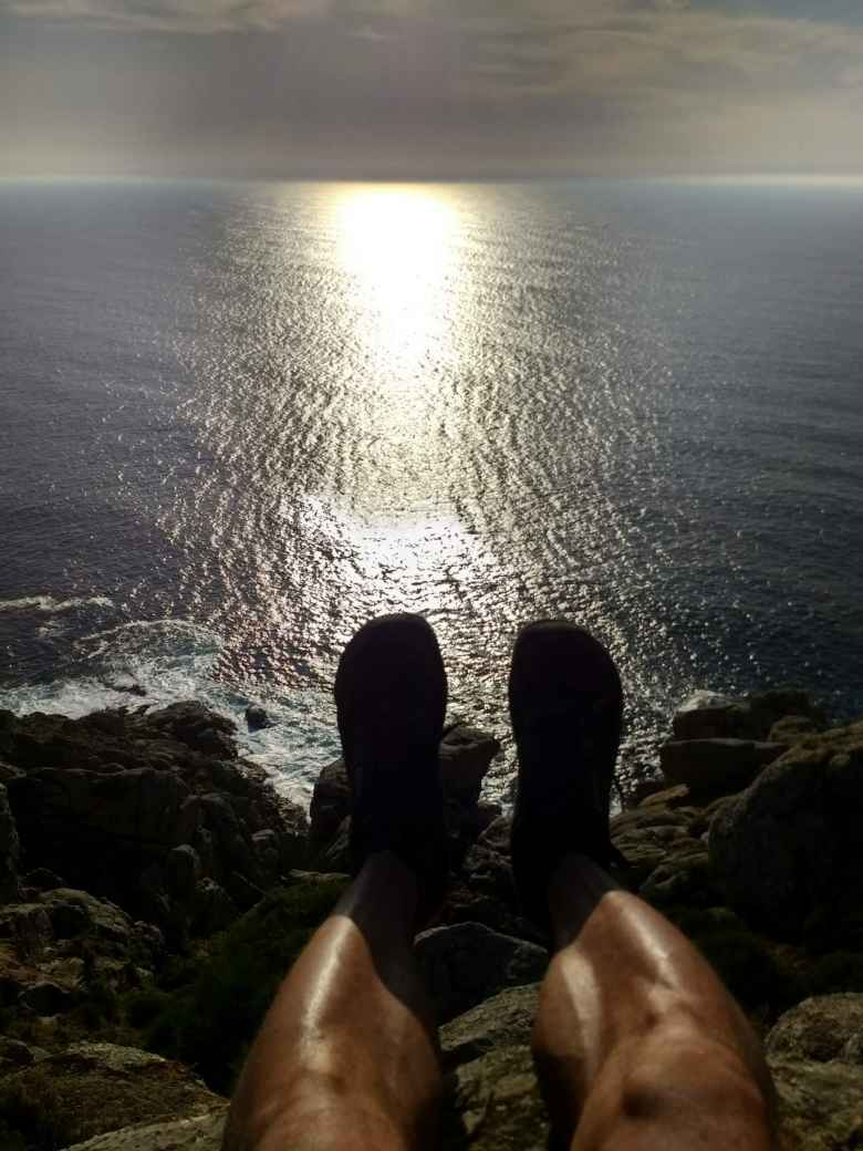 Felix Wong's legs and feet overhanging a rocky cliff on the western shoreline of Fisterra, sun reflecting off the Atlantic Ocean
