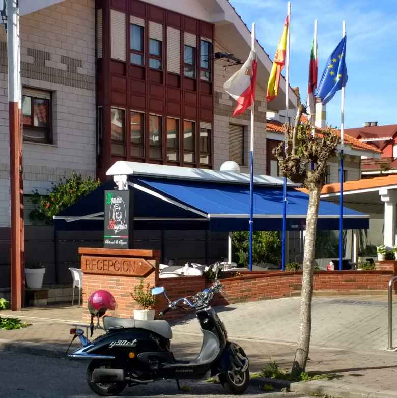 A scooter outside a hotel with flags in Galizano, Spain.