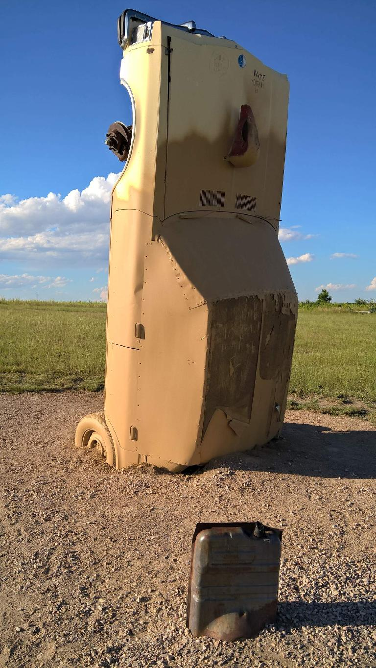 Tan car sticking out of the mud at Carhenge.