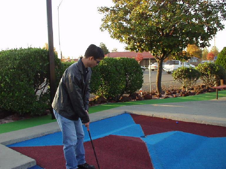 Felix, the Tiger Woods-beater (not), showing Carolyn how it's done (again, not) at Golfland in Stockton. (November 11, 2002)