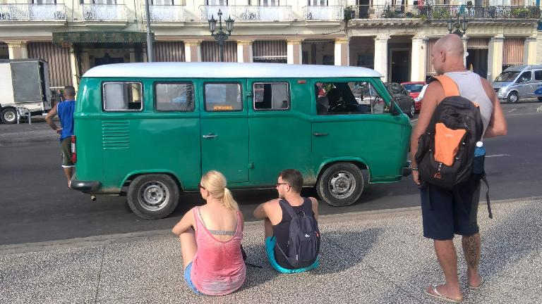 A green 1960s Volkswagen Bus with white top in front of Hotel Inglaterra in Havana, Cuba.