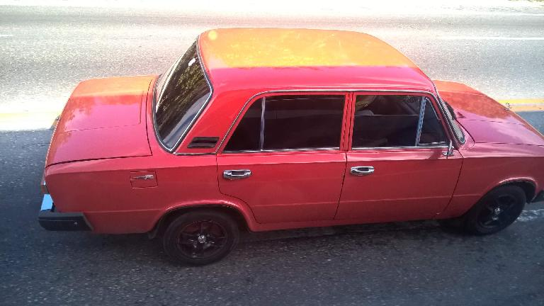 "A red/orange Lada sedan with Honda ""Type R"" logos as seen east of Havana, Cuba."