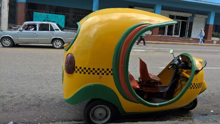 A yellow/green three-wheeled taxi in Havana, Cuba.