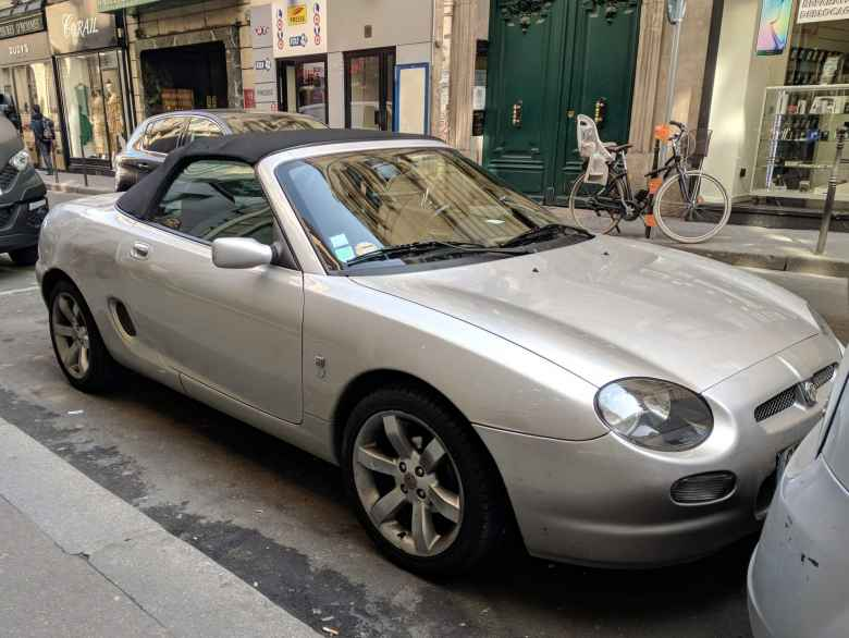 A silver MGF convertible parked on a street in Paris.