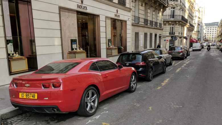 A red, fifth-generation Chevrolet Camaro on a street in Paris.