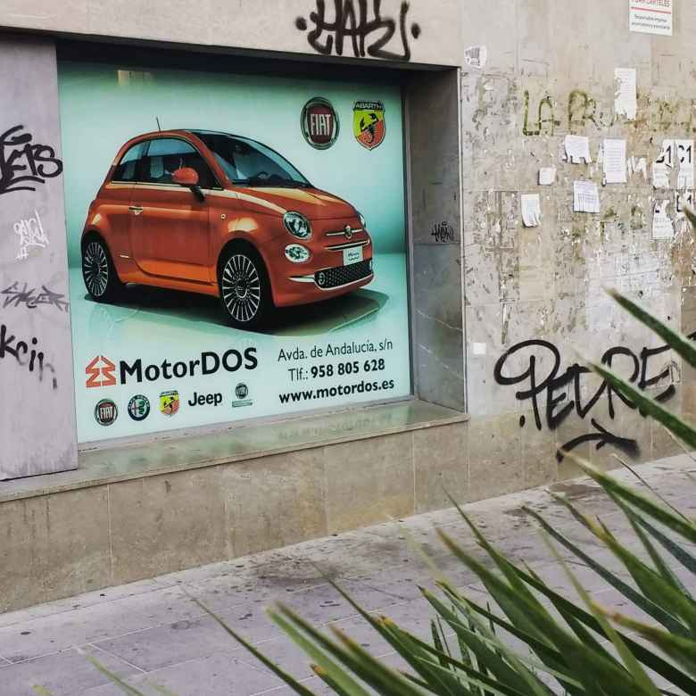 A billboard for a red Fiat 500 in Granada, by MotorDOS.